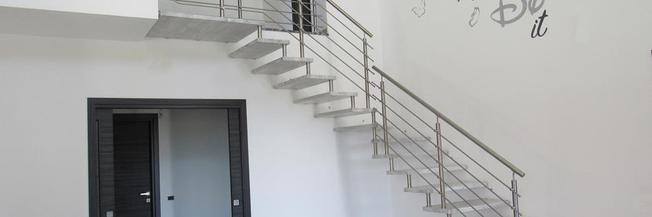 Scala con gradini legno e corrimano acciaio